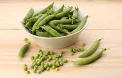 Green peas and pea pods in white dish on wooden table