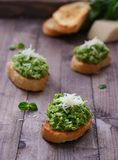 Green peas pesto with mint. Pesto green peas with mint on slices of toasted bread Stock Image