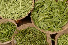 Green peas in pods pile lies in the baskets for sale on market. Green peas in pods pile lies in the baskets for sale on the market Royalty Free Stock Photo