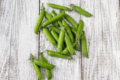 Green peas pods on a white wooden table. Top view Royalty Free Stock Photos