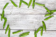 Green peas pods on a white wooden table. Top view, copy space Royalty Free Stock Image