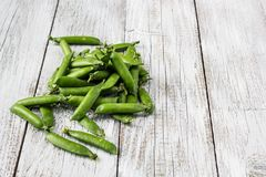 Green peas pods on a white wooden table. Top view, copy space Stock Photography