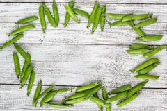 Green peas pods on a white wooden table. Top view, copy space Stock Photos