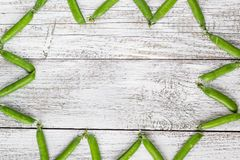 Green peas pods on a white wooden table. Top view, copy space Royalty Free Stock Photos