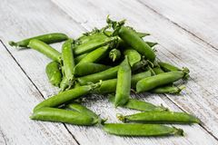 Green peas pods on a white wooden table. Top view Royalty Free Stock Images