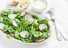 Green peas, radish and baby spinach salad on ceramic plate on a light background. Stock Image