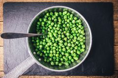 Green peas on silver frying pan stock images