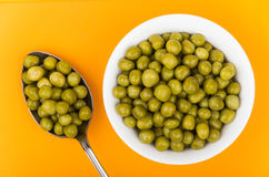Green peas in small glass bowl and spoon Royalty Free Stock Photography