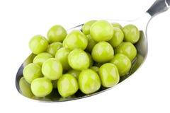 Green peas on spoon Stock Photos