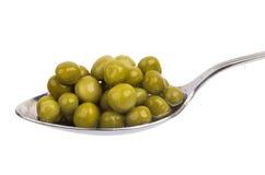 Green peas in steel spoon Royalty Free Stock Images