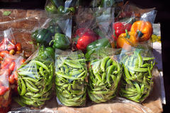Green peas, sweet pepper and tomato in a plastic bag. Sale at local market Royalty Free Stock Photo