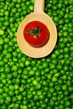 Green peas and tomato on a wooden spoon royalty free stock images
