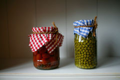 Green peas and tomatoes. Canned green peas and tomatoes in the bank on the shelf in the pantry Stock Photo