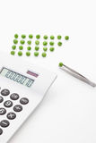 Green peas with tweezer and calculator on white background Royalty Free Stock Images