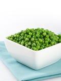 Green peas on white. Green peas in a white bowl on a light blue napkin. White background Royalty Free Stock Photo