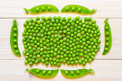 Green peas in white bowl on wooden background, top view or flat stock photo