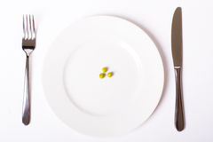 Green peas on white plate Royalty Free Stock Image