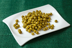 Green peas on a white plate Royalty Free Stock Photos