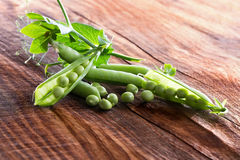 Green peas on the wooden background Royalty Free Stock Images