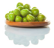Green Peas On Wooden Spoon III. Green peas on wooden spoon over white background stock photo