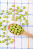 Green peas in a wooden spoon Royalty Free Stock Images