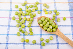 Green peas in a wooden spoon Royalty Free Stock Photo