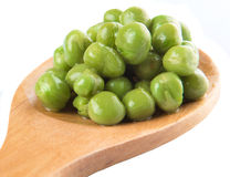 Green Peas On Wooden Spoon XIII. Green peas on wooden spoon over white background royalty free stock photos