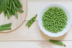 Green peas on wooden table with copy space. White plate with peeled beans inside. Round kitchen board with whole pods on it. Natural organic food concept. Raw royalty free stock photos