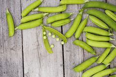 Green peas on wooden table. One opened Royalty Free Stock Photos