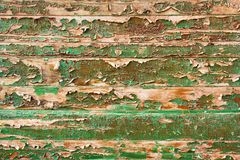 Green peeling paint on the wooden fence. Green peeling paint on the brown horizontal wooden fence royalty free stock photo