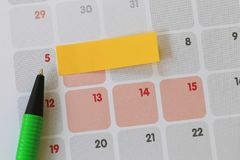 Green pen points to a five number of calendar and have blank yel. Low note paper for design concept of important day in you work Stock Images
