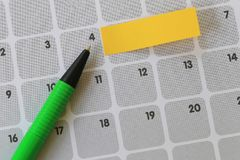 Green pen points to a four number of calendar and have blank yel. Low note paper for design concept of important day in you work Stock Images