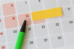 Green pen points to a fourteen number of calendar and have blank. Yellow note paper for design concept of important day in you work Stock Photography