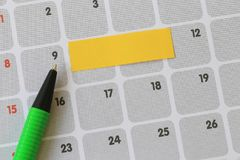 Green pen points to a nine number of calendar and have blank yel. Low note paper for design concept of important day in you work Royalty Free Stock Photo