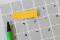 Green pen points to a one number of calendar and have blank yell. Ow note paper for design concept of important day in you work Royalty Free Stock Images