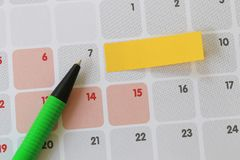 Green pen points to a seven number of calendar and have blank ye. Llow note paper for design concept of important day in you work Royalty Free Stock Image