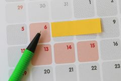 Green pen points to a six number of calendar and have blank yell. Ow note paper for design concept of important day in you work Stock Photos
