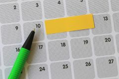 Green pen points to a ten number of calendar and have blank yell. Ow note paper for design concept of important day in you work Royalty Free Stock Photos