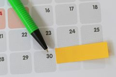 Green pen points to a thirty number of calendar and have blank y. Ellow note paper for design concept of important day in you work Stock Photos