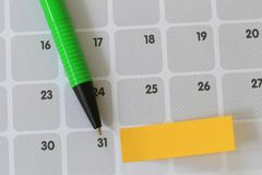 Green pen points to a thirty one number of calendar and have bla. Nk yellow note paper for design concept of important day in you work Stock Images