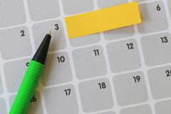 Green pen points to a three number of calendar and have blank ye. Llow note paper for design concept of important day in you work Stock Photos