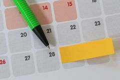 Green pen points to a twenty eight number of calendar and have b. Lank yellow note paper for design concept of important day in you work Royalty Free Stock Photos