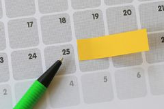 Green pen points to a twenty-five number of calendar and have bl. Ank yellow note paper for design concept of important day in you work Stock Image