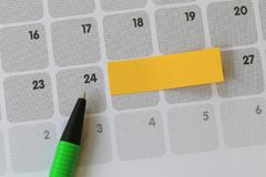 Green pen points to a Twenty-four number of calendar and have bl. Ank yellow note paper for design concept of important day in you work Stock Photos