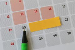 Green pen points to a twenty number of calendar and have blank y. Ellow note paper for design concept of important day in you work Stock Image