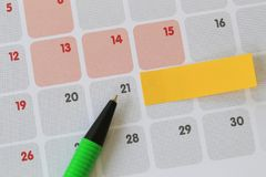 Green pen points to a twenty-one number of calendar and have bla. Nk yellow note paper for design concept of important day in you work Royalty Free Stock Photos