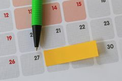 Green pen points to a twenty seven number of calendar and have b. Lank yellow note paper for design concept of important day in you work Stock Photos