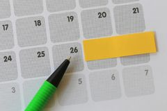 Green pen points to a twenty six number of calendar and have bla. Nk yellow note paper for design concept of important day in you work Stock Photos