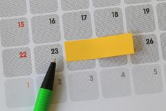 Green pen points to a Twenty-three number of calendar and have b. Lank yellow note paper for design concept of important day in you work Stock Image