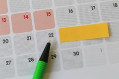 Green pen points to a Twenty-two number of calendar and have bla. Nk yellow note paper for design concept of important day in you work Stock Images